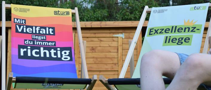 """""""Mit Vielfalt liegt du immer richtig."""" Der andere leere Liegestuhl ist hellgrün. Darauf steht """"Exzelenzliege"""". Über dem Wort ist eine kleine Krone. Auf beinden Liegestühlen ist oben links das TU Dresde-Logo und oben rechts das StuRa-Logo zu sehen."""